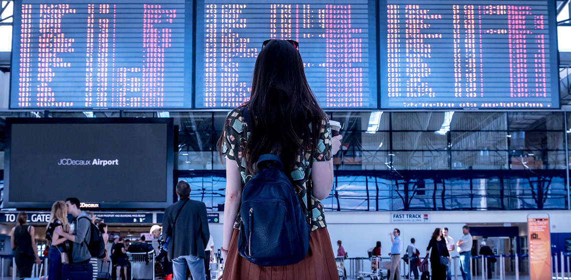 woman looking at airport boards // 5 Tips to Make Flying While Pregnant Easier