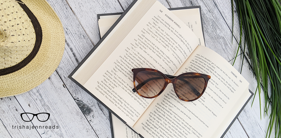 sunglasses on some open books with a sun hat and greenery
