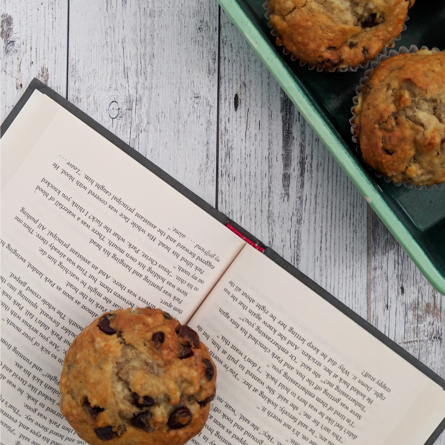 Banana chocolate chip muffins on an open book.