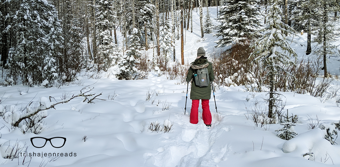 a woman snowshoeing in the woods with a grey backpack