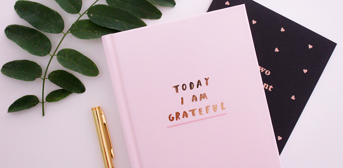 "Pink journal that says ""today I am grateful"" beside a pen and a leafy branch."