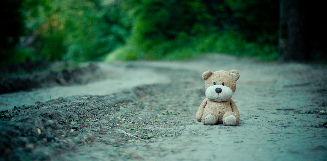 a teddy bear sitting alone on a road