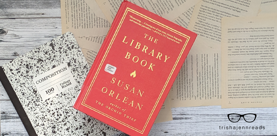 The Library Book by Susan Orlean on top of a composition notebook and some loose book pages