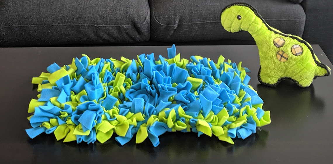 a snuffle mat beside a toy dino plush