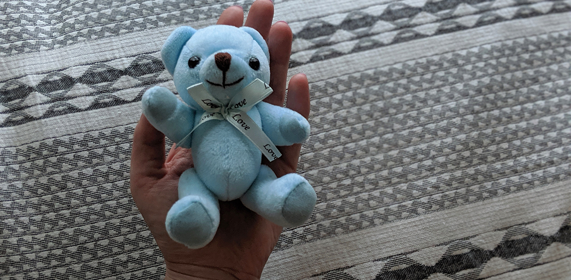 A hand holding a tiny blue teddy bear.