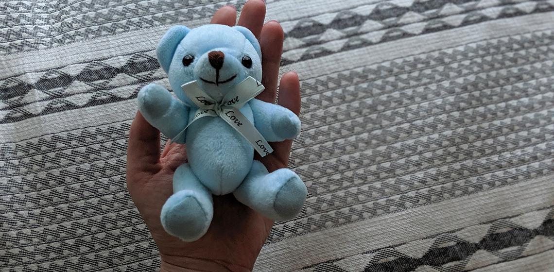 A hand holding a tiny blue teddy bear.
