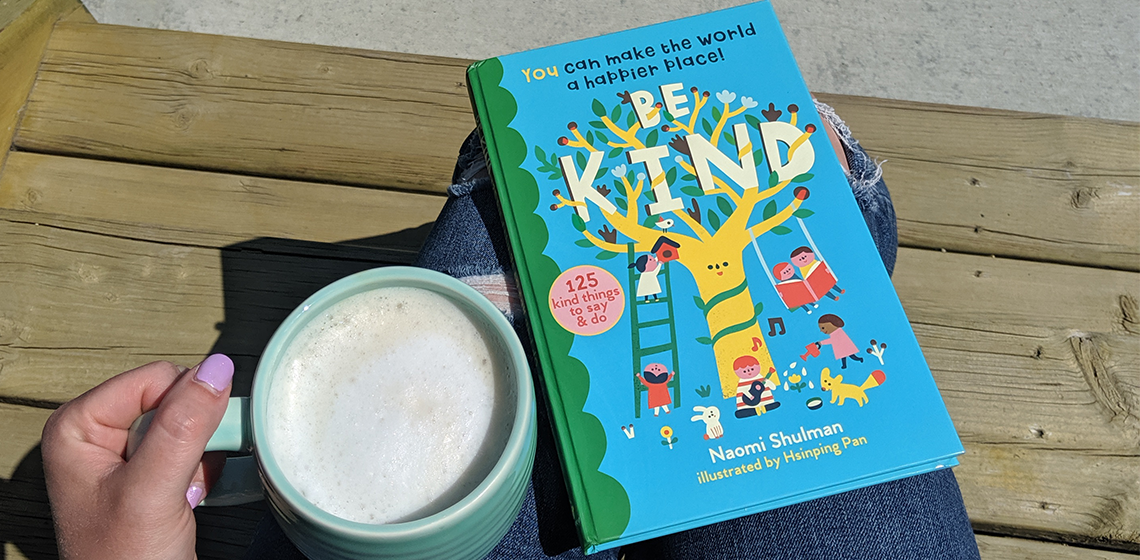 Be Kind book on a wooden step beside a teal coffee cup