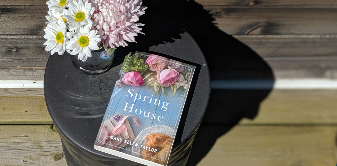 Image: Cover of Spring House by Mary Ellen Taylor beside some daisies on a grey pedestal table on a wooden surface
