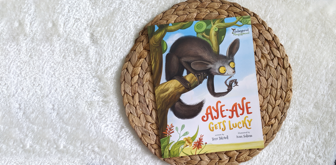 Illustrated cover of Aye-Aye Gets Lucky picture book on a white rug