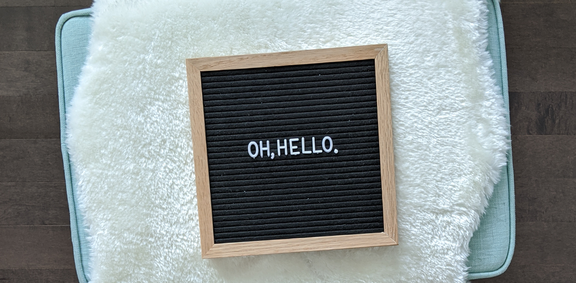 "a felt letter board with the words ""oh, hello."" resting on an ottoman"