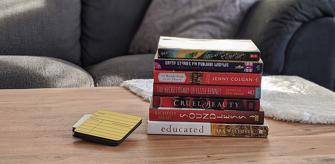 a stack of book on a coffee table in front of a couch