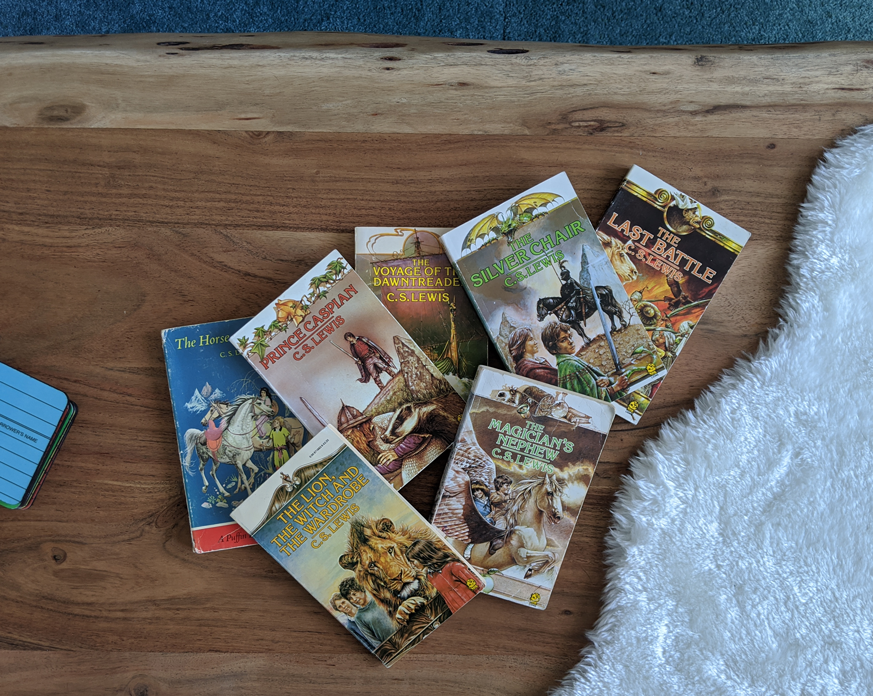 The Chronicles of Narnia book series on a wood coffee table.