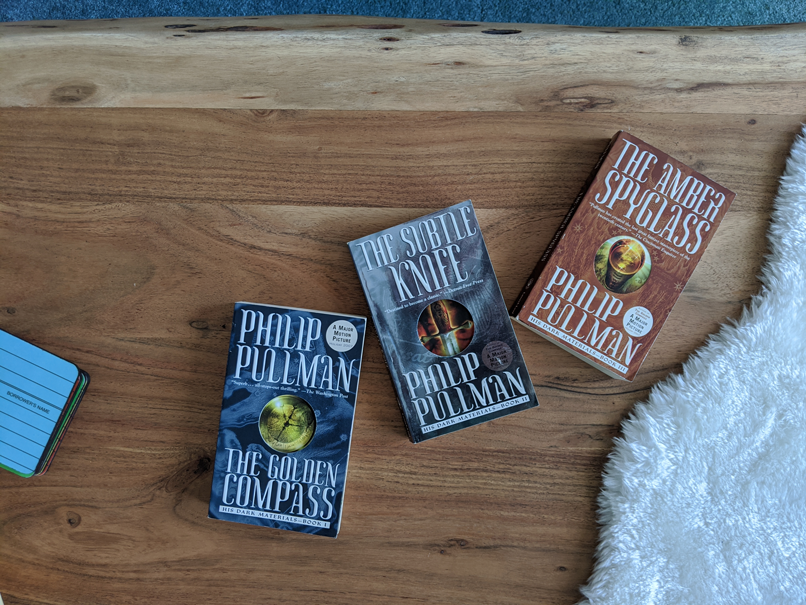 His Dark Materials series by Philip Pullman on a wood coffee table
