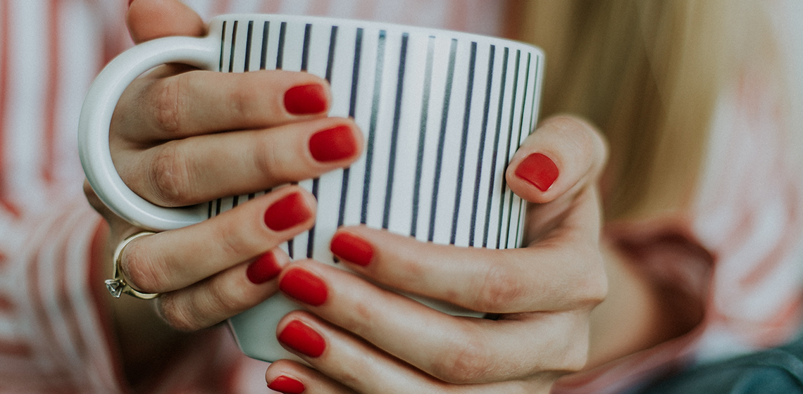 a woman with red nail polish holding a coffee cup in both hands
