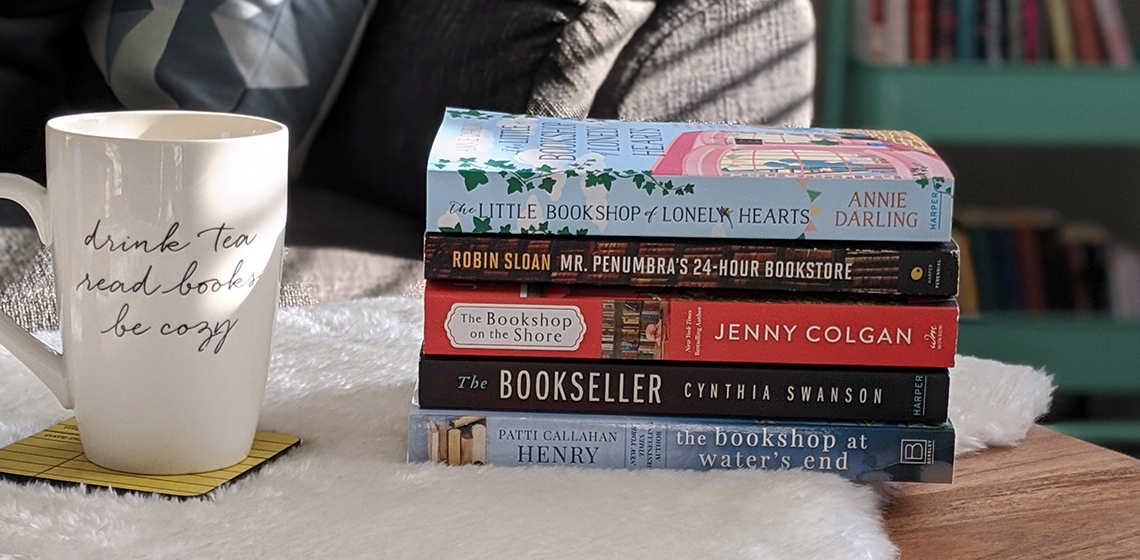 A stack of paperback books beside a coffee mug that says Read Books Drink Tea Be Cozy