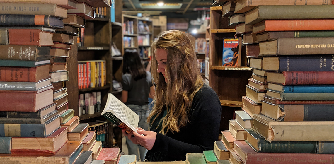 a woman reading, surrounded by a sculpture of books