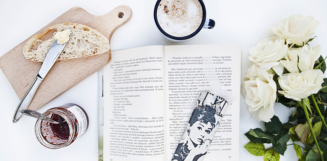 An open book surrounded by bread, jam, a coffee, and roses. An audrey hepburn bookmark.