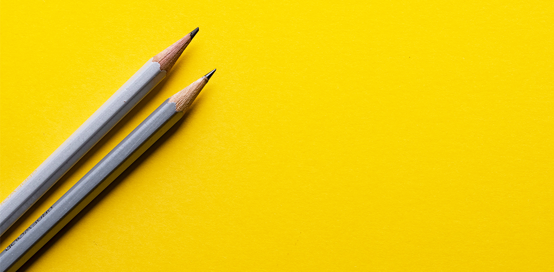 two grey pencils on a yellow background